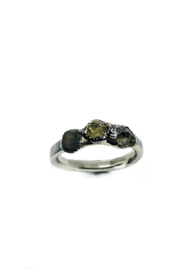The beautiful yellow/green rough sapphire center stone pops in the middle between two blue uncut sapphires. The band is textured silver with a patina finish. It gives it some sparkle but doesn't take away from its organic, rustic look.