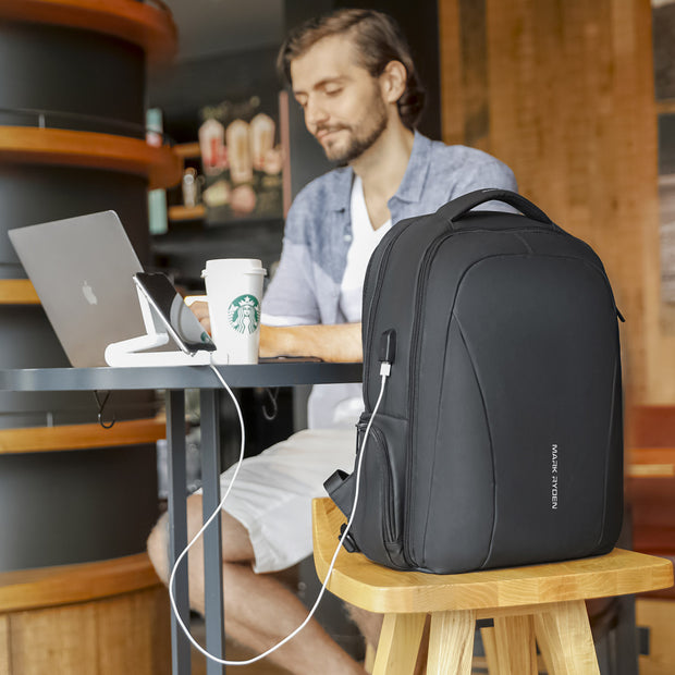 Man in cafe with minimal black USB charging backpack from Mark Ryden.