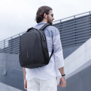 Man wearing minimal black USB charging backpack from Mark Ryden.