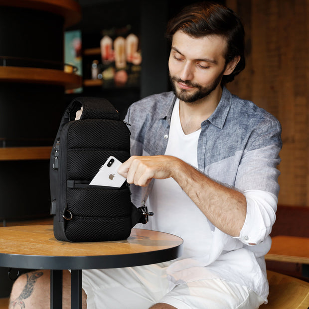 Man with Mark Ryden Crypto usb charging waterproof sling bag in black.