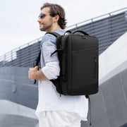 Man wearing Mark Ryden Infinity XL Rain usb charging business / travel backpack.