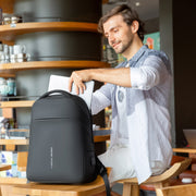 Man in cafe with Mark Ryden Limit anti-theft usb charging backpack.