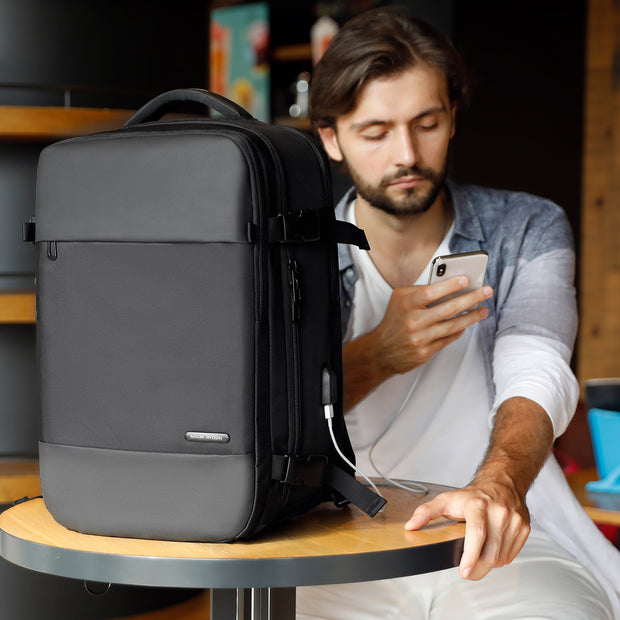 Man in cafe with Mark Ryden Nomad usb charging travel backpack.