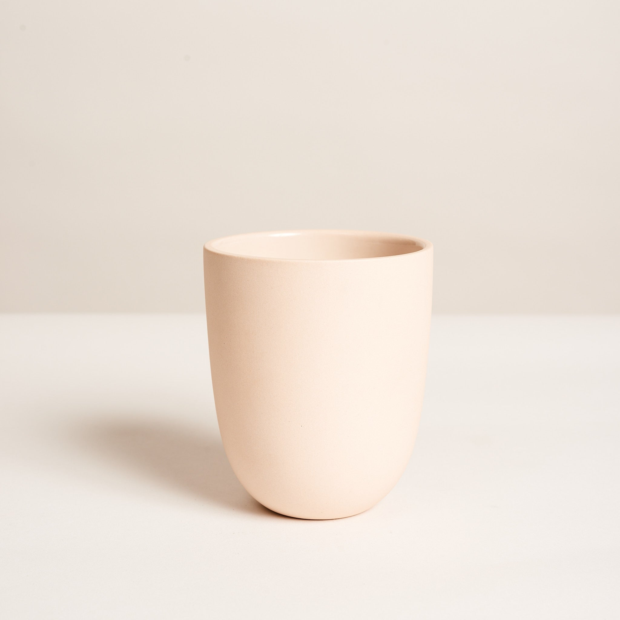 "Small tumbler in blush slipcast from a hand-thrown design with a raw, sanded exterior and interior gloss lined glaze for easy cleaning.  4.5"" high and 3.5"" diameter at opening. 14 oz capacity."