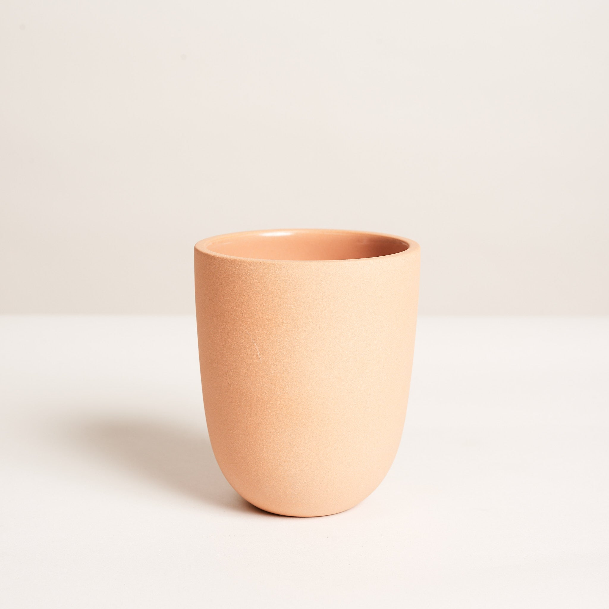 "Small tumbler in terracotta slipcast from a hand-thrown design with a raw, sanded exterior and interior gloss lined glaze for easy cleaning.  4.5"" high and 3.5"" diameter at opening. 14 oz capacity."