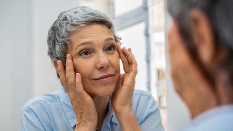 Photo showing a lady with short grey hair wearing a light blue top and looking in the mirror