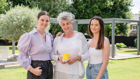 Photo showing Maxine, Margot and Darcy Laceby standing in a garden and smiling