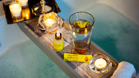 Photo showing a relaxing bubble bath with a wooden bath tray that contains candles, a latte glass, Absolute Collagen sachet and Maxerum bottle