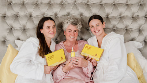 Photo showing Maxine, Margot and Darcy Laceby smiling at the camera, they are sitting against a grey velvet headboard and wearing dressing gowns and they are holding up Maxerum bottles and Absolute Collagen boxes