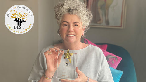 Photo showing Maxine Laceby sitting in front of some framed art and holding up a Best Business Woman awards trophy, she is wearing a grey top and smiling, and the Best Business Woman awards logo is visible in the top left