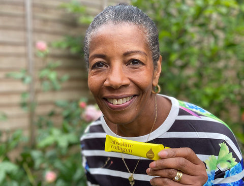 Photo of a smiling Black woman with short hair and a striped t-shirt, she is holding up a yellow Absolute Collagen sachet