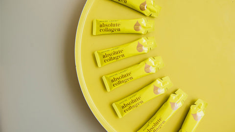 Photo showing a crescent of Absolute Collagen sachets lying flat on a yellow and grey background
