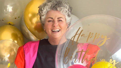Photo showing Maxine Laceby holding balloons and standing against a background of gold balloons, she is wearing a brightly coloured dress and smiling widely