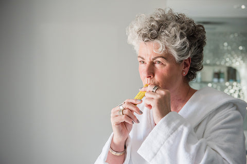 Photo of a white woman with short silver hair wearing a white dressing gown and squeezing a yellow Absolute Collagen sachet into her mouth