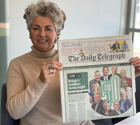 Photo showing a white woman with short silver hair smiling and holding up a copy of The Daily Telegraph, which has a photo of her on the page