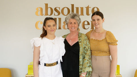 Photo showing a smiling Maxine, Margot and Darcy Laceby standing in front of a large copper Absolute Collagen sign