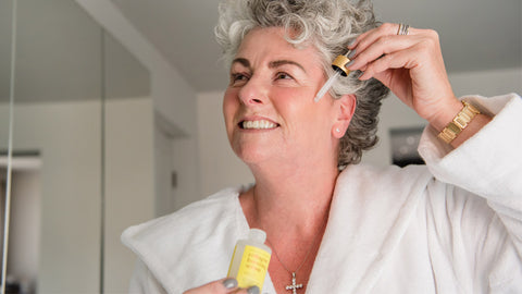 Photo showing Maxine Laceby wearing a white dressing gown and applying Maxerum to her face while smiling into a mirror