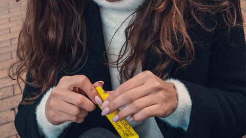Photo of a woman with long wavy brown hair, she is holding a yellow Absolute Collagen sachet in her hands