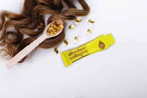 Photo of brown hair alongside a spoonful of vitamins and a yellow Absolute Collagen sachet
