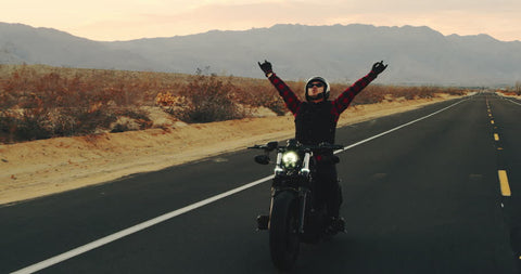 Motorcycle rider with a happy gesture