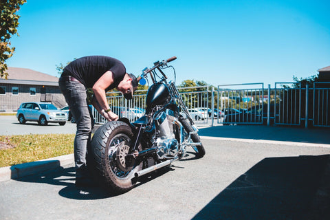 man maintaining his motorcycle tires