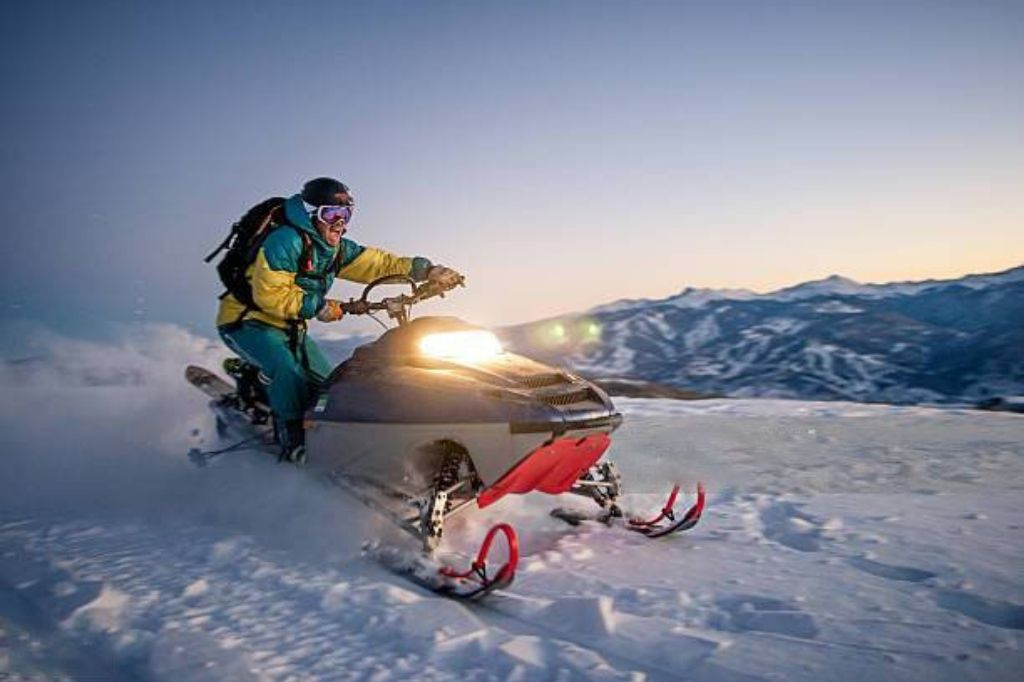 snowmobile with rider in snow during sunset