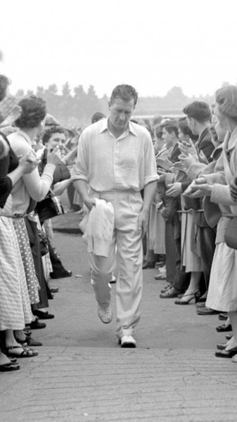 Jim Laker walking off the field wearing classic cricket whites