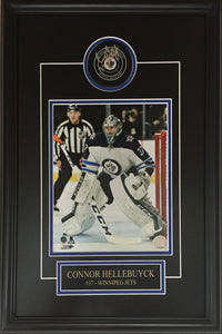 Connor Hellebuyck Autographed Winnipeg Jets Puck Framed with Road Jersey Photo