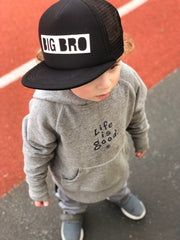 "Model Kai is wearing the ""Big Bro"" Black Custom Block Letters Trucker Hat"
