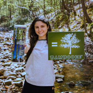 girl holding roll and picture of tree to represent the fact that we plant trees