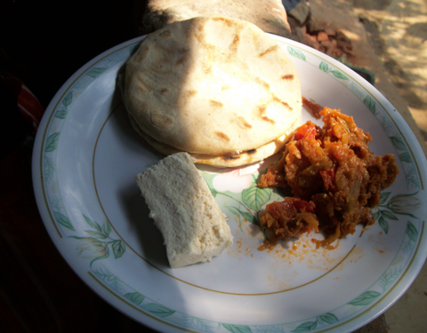 Two tortillas, a small piece of bread and tomatada (a mix of tomato, onions and garlic)