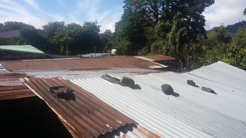 Most coffee pickers live in small homes with tin roofs. Here you see rocks placed so that the roof does not blow off during storms. Elba paid to have new roofing installed for a family of coffee pickers in El Salvador.