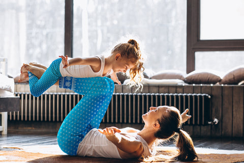 A mother and her small daughter doing yoga in their living room in matching outfits