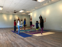 An instructor and students practicing Hatha Yoga in a studio