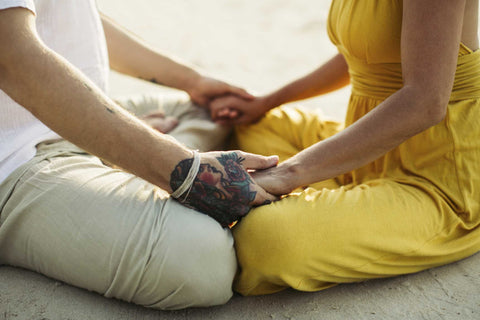Couple in meditation together, hand in hand.
