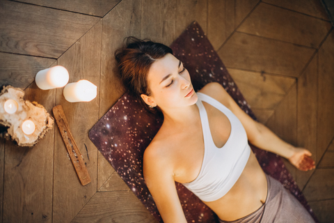 Young woman relaxing in Shavasana after a de-stressing yoga session.
