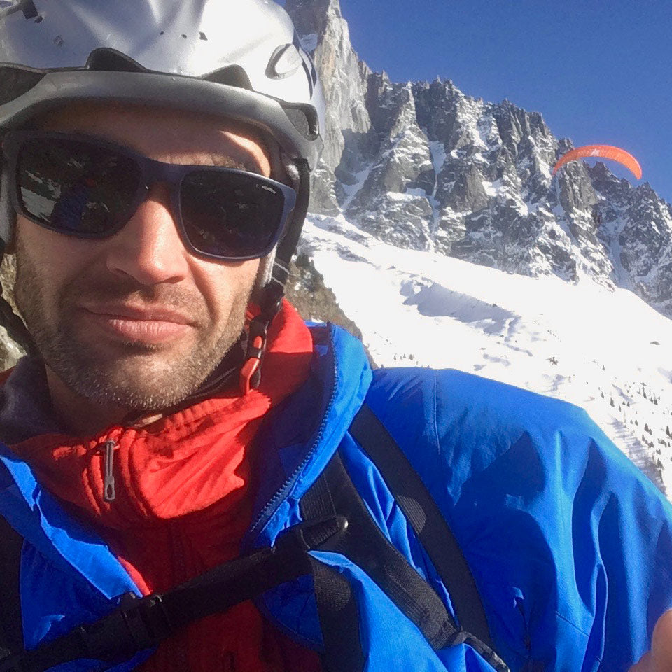 Chris Warner paragliding in Chamonix. Wearing Grid Pro Hoodie underneath Guide PrimaLoft Hoodie
