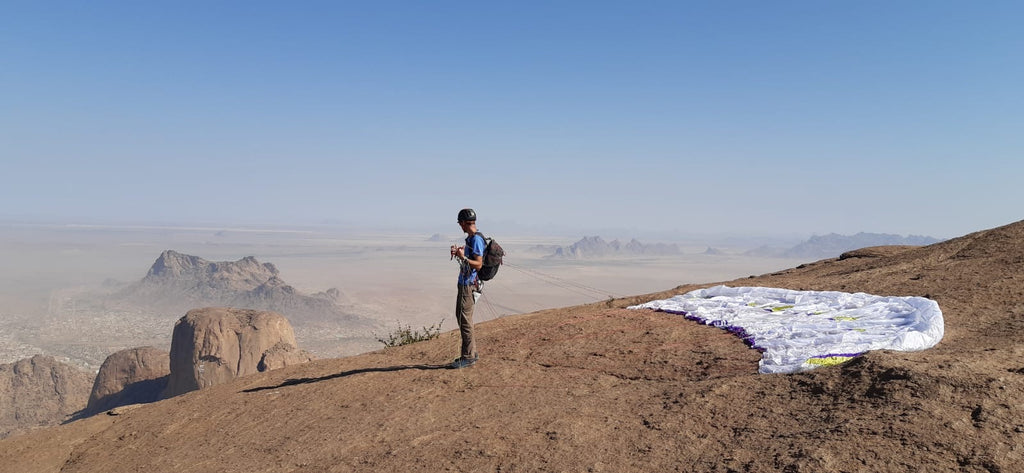 Climb up, paraglide down in Kassala, Sudan. Chris wears Mojo Stretch Pants and Run Power Dry Crew