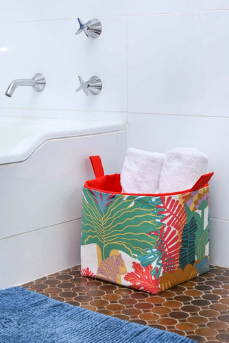 bath towels rolled like spa towels and stored in a large tropical cube storage basket next to bathtub, bathroom towel storage