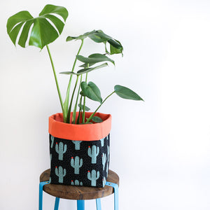 monstera plant in a black and orange cactus fabric plant pot cover