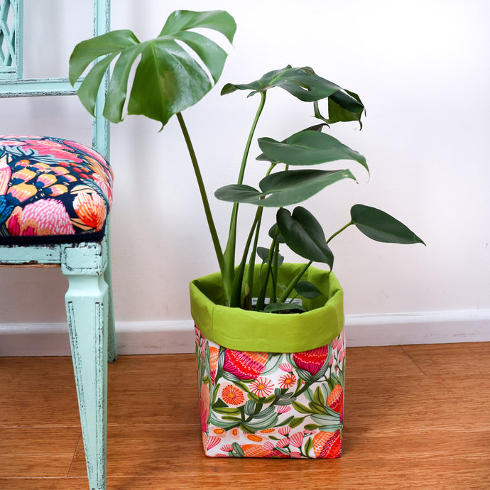 monstera plant in bright green multi-coloured square fabric pot plant cover next to a mint chair-australiana homewares
