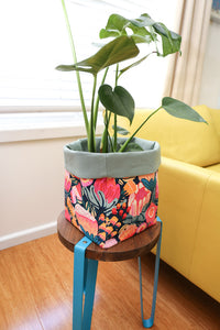pink protea blossom large fabric pot plant holder on stool next to yellow sofa