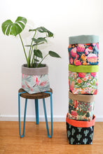 Load image into Gallery viewer, stack of multi-coloured square fabric planters with monstera plant