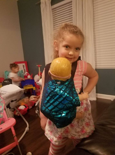 Little girl a using a mer doll carrier