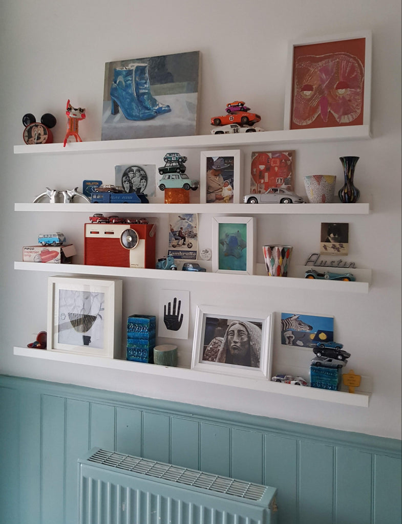 Small objects arranged on white shelves