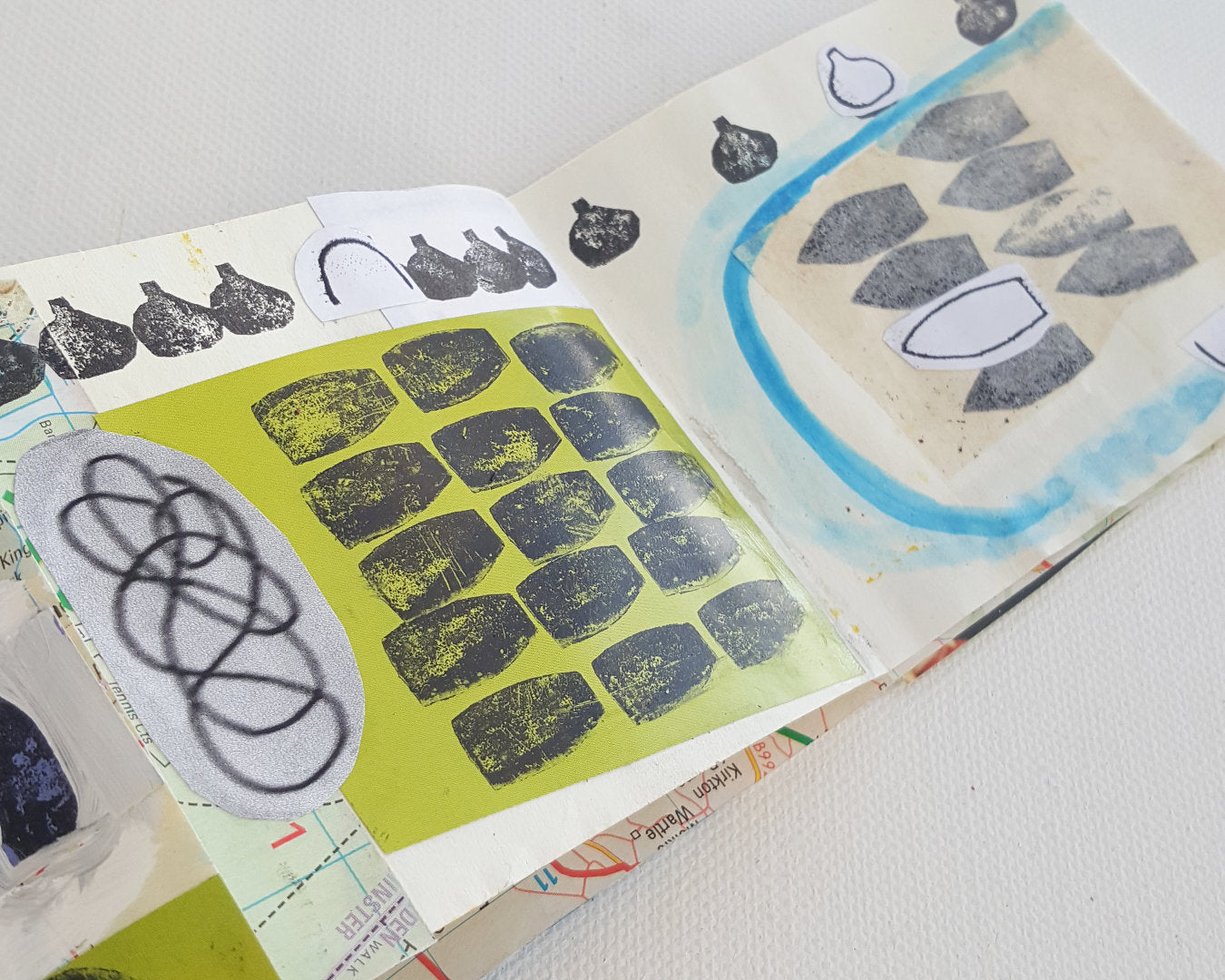 Handmade sketchbook open showing 2 pages of collage and hand stamps.