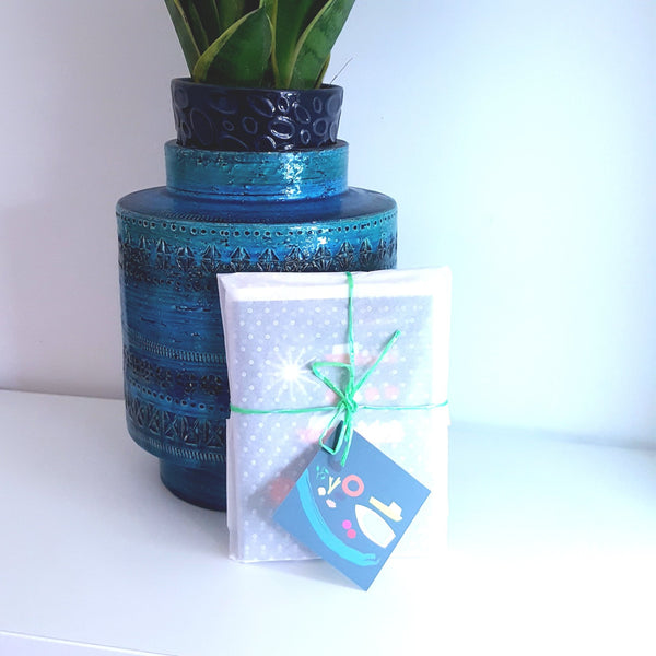 Set of 5 greeting cards, wrapped in tissue paper, resting against a teal ceramic plant pot.