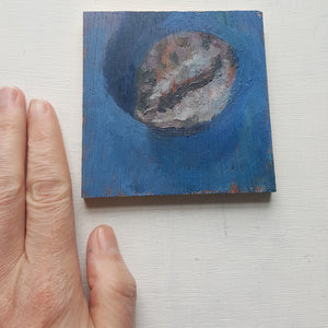 cowrie shell painting with my hand beside it for scale.