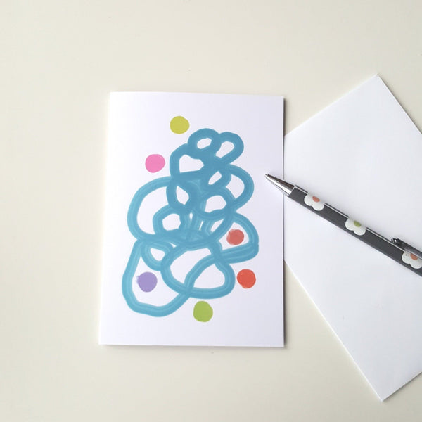 greeting card on white desk with white envelope and pencil.