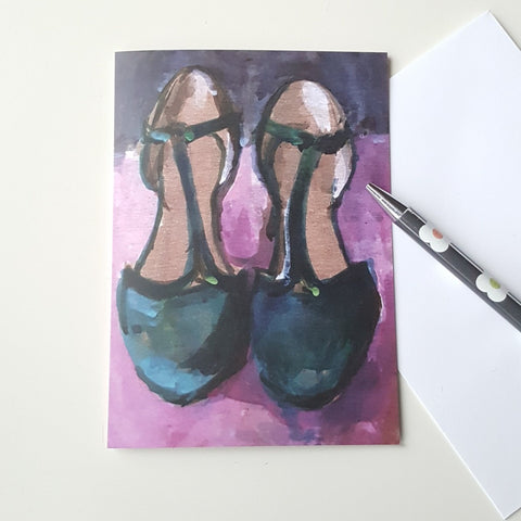 shoes greeting card on white desk with pen and evelope.